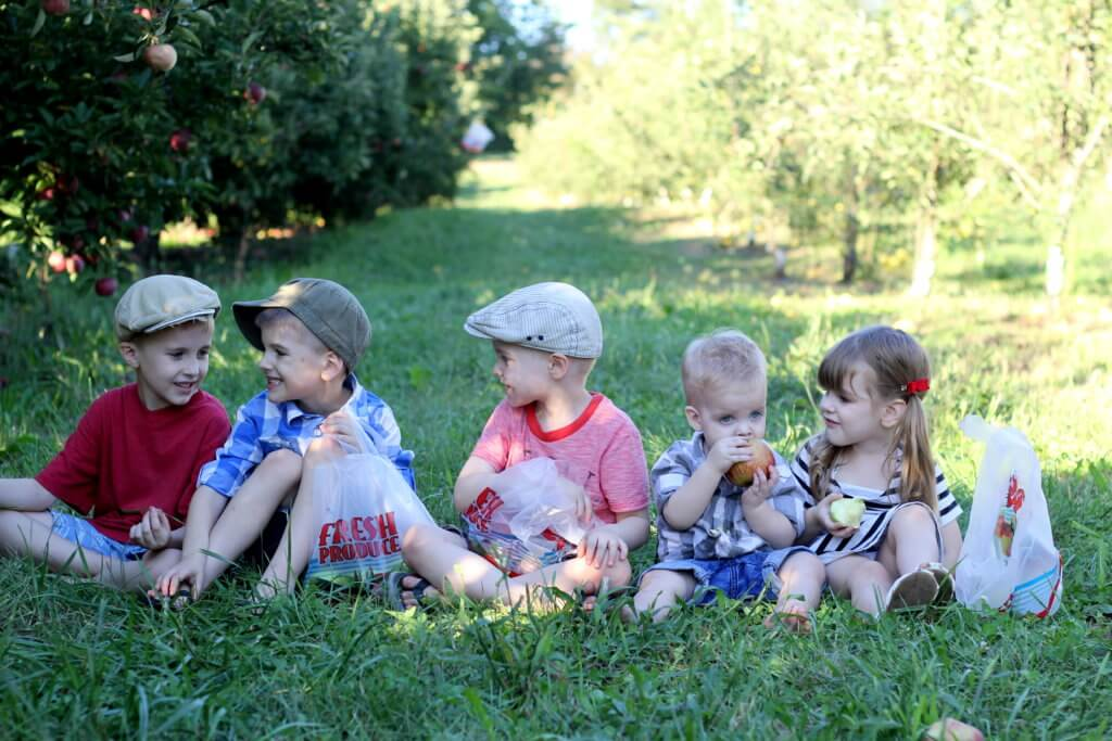 5 kids sitting in the grass