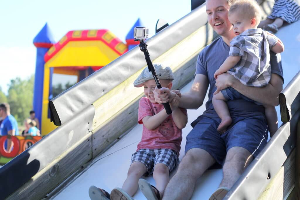 dad and boys going down a slide
