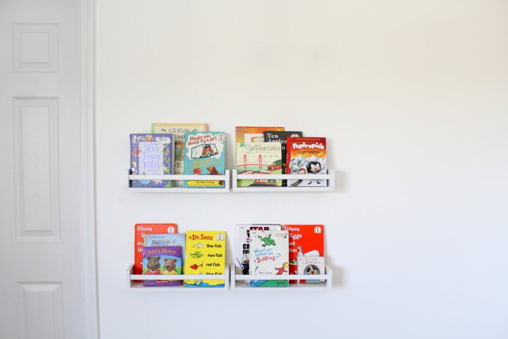 4 little white bookshelves on the wall with kids books