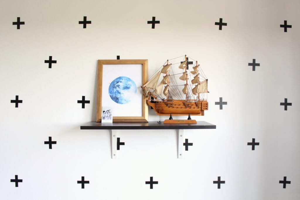 toy sail boat and moon picture on shelf with washi tape plus signs on wall