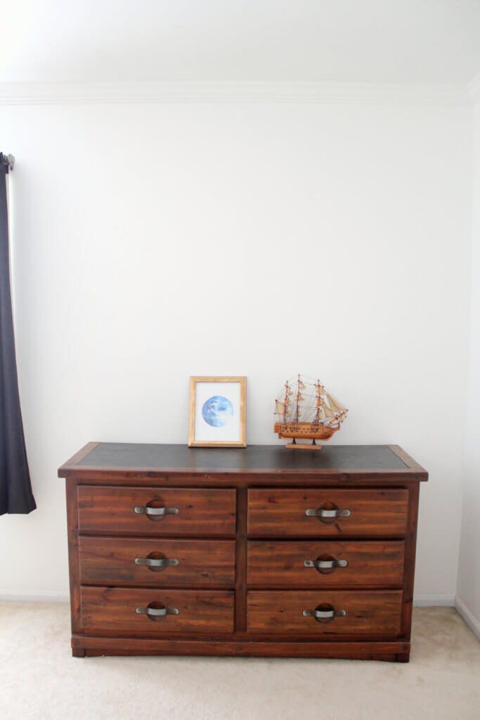toy boat and blue moon picture on dresser