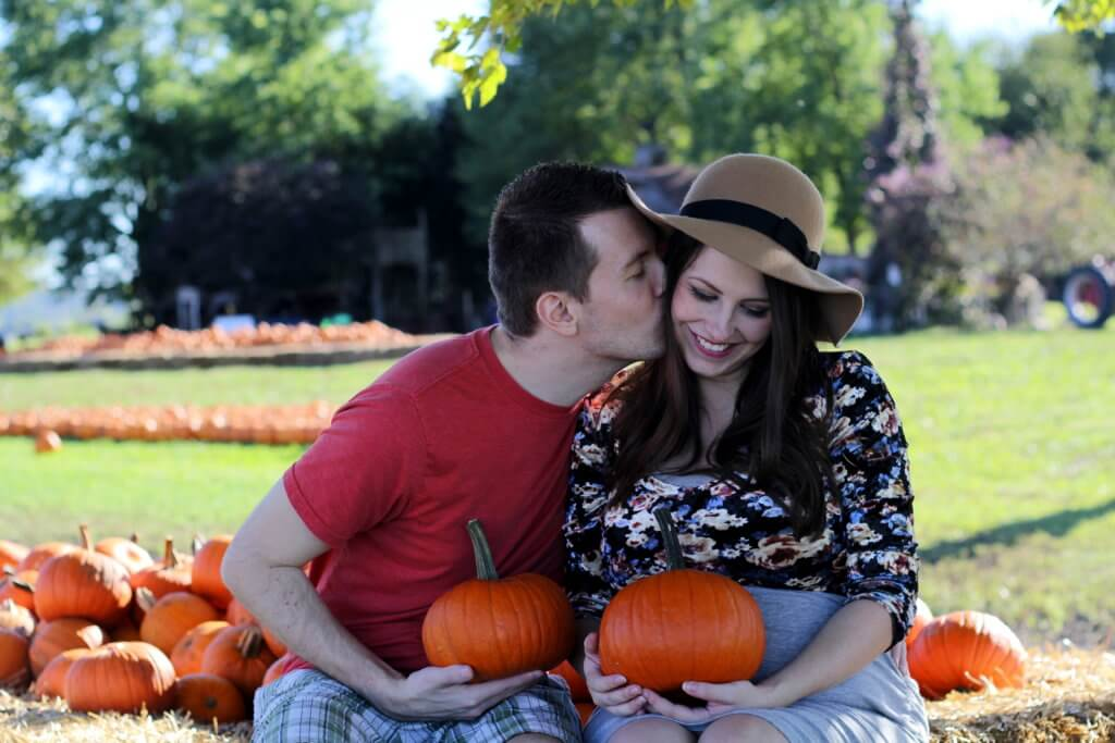 married couple kissing at the pumpkin patch