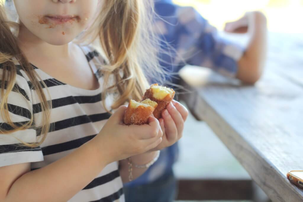 toddler girl eating an apple cinnamon donut