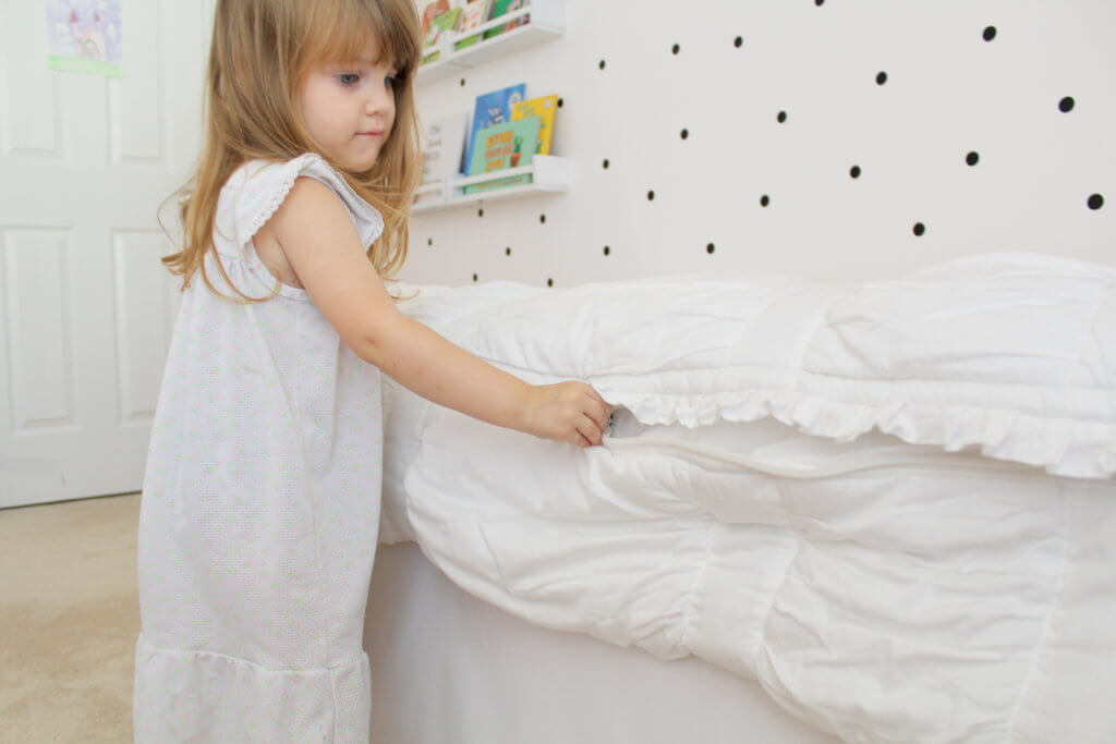 little girl zipping up bed sheets