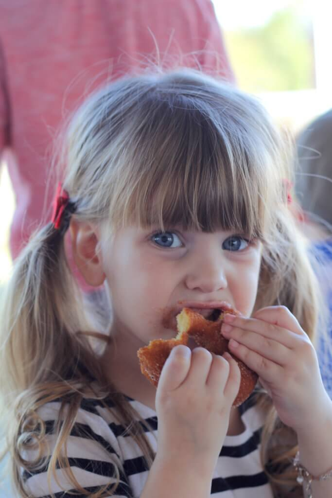 girl taking bites of the donut