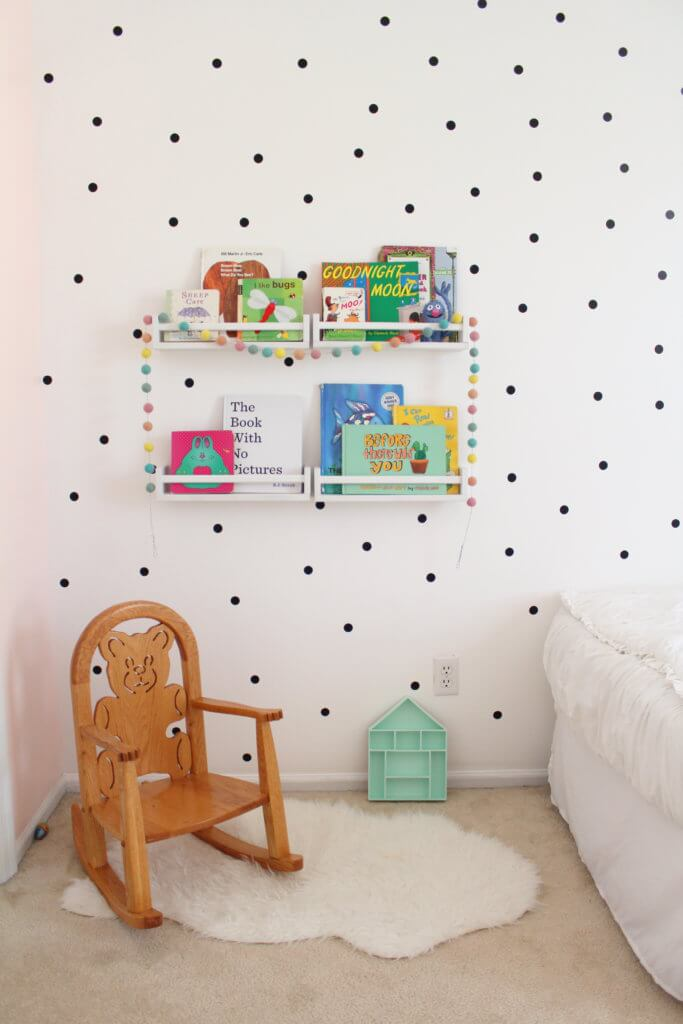 little white bookshelves on wall with children's books