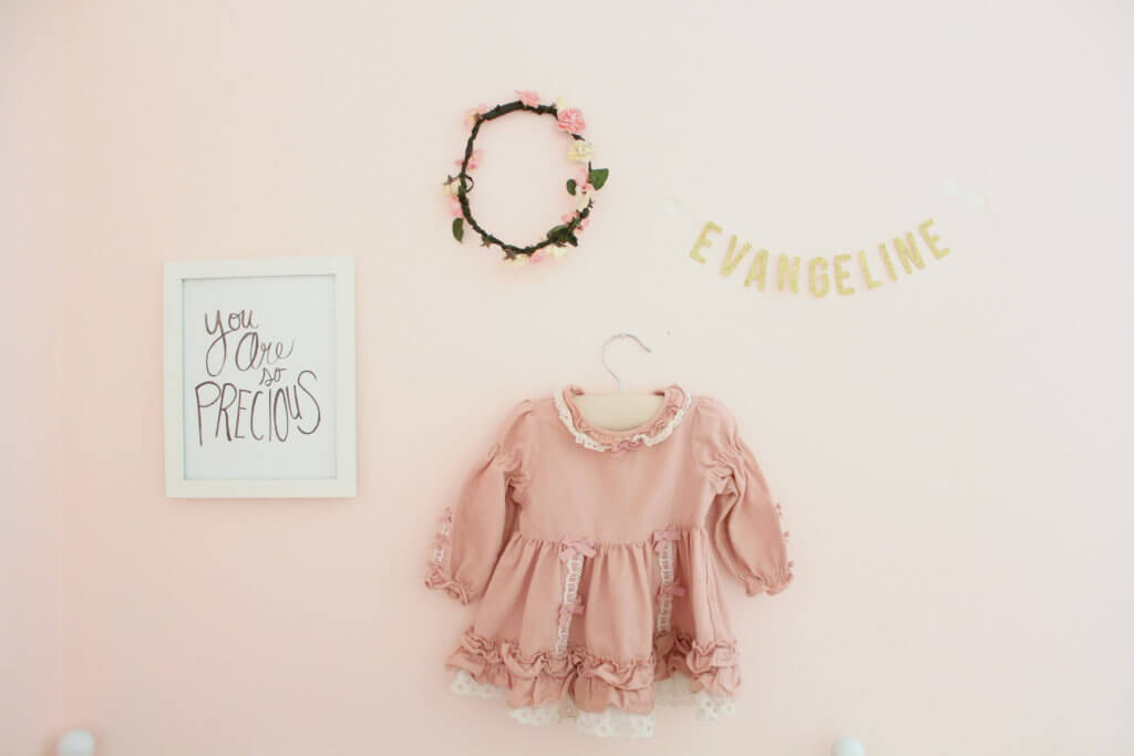 name banner flower crown vintage dress and picture hanging on the wall